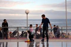 Een klein meisje en haar vader zijn ijs schaatsend op Bondi-ijsbaan Stock Foto's