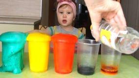 Een klein meisje experimenteert en verrast stock video