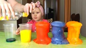 Een klein meisje experimenteert en verrast stock footage
