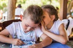 Een klein meisje fluistert iets aan een mooie jongen in een straatrestaurant royalty-vrije stock foto