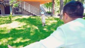 Een klein meisje gaat naar de papa op het groene gras, draaien in één plaats en dalingen, een tijdverdrijf van de pretfamilie, va stock videobeelden
