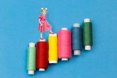 Een klein meisje gaat op rollen met gekleurde draden stock afbeeldingen