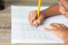 Een klein meisje gebruikt een geel potlood schrijvend in een notitieboekje stock fotografie