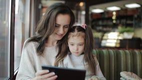 Een klein meisje gebruikt WiFi op een tablet in een koffie de moeder en haar dochter houden een gadget in hun handen stock footage
