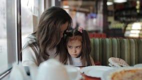 Een klein meisje gebruikt WiFi op een tablet in een koffie de moeder en haar dochter houden een gadget in hun handen stock video