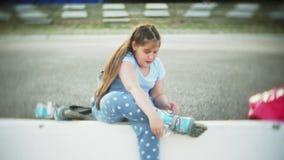Een klein meisje in een helm en een defensie schaatst op rolschaatsen Het kind rolt op de rollen in het park Het meisje leert stock video