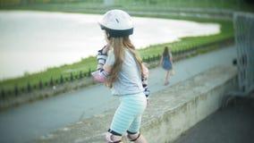 Een klein meisje in een helm en een defensie schaatst op rolschaatsen Het kind rolt op de rollen in het park Het meisje leert stock footage