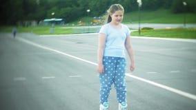 Een klein meisje in een helm en een defensie schaatst op rolschaatsen Het kind rolt op de rollen in het park Het meisje leert stock videobeelden