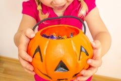 Een klein meisje houdt een pompoen met suikergoed in haar handen en rekt het uit om zelfs nog meer suikergoed voor Halloween te k stock afbeelding