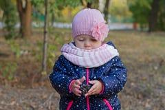 Een klein meisje houdt een sparappel in het park stock afbeeldingen