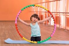 Een klein meisje is 5 jaar oud in de gymnastiek Stock Fotografie