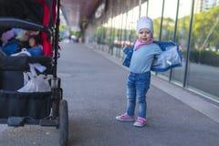 Een klein meisje in jeansslijtage toont op de straat Stock Foto