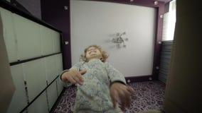Een klein meisje kijkt in de doos, is verrast en gelukkig om een verrassing te ontvangen stock videobeelden