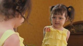 Een klein meisje kijkt in de spiegel Een mooi meisje met staarten op haar hoofd leunt voor de spiegel Een kind in een geel stock footage