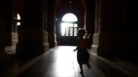 Een klein meisje in een kleding loopt langs de donkere gang onder de kolommen het spelen loopt de achterstand in stock videobeelden