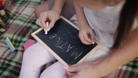 Een klein meisje leert om woorden op het bord met krijt te schrijven Het mamma onderwijst dochter om brieven, alfabet te schrijve stock video