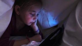 Een klein meisje let op een beeldverhaal dat op een tablet met een deken wordt behandeld De glimlachen, verheugt zich overwinning stock footage