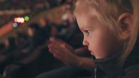 Een klein meisje let op prestaties in een circus toejuichend haar handen stock videobeelden