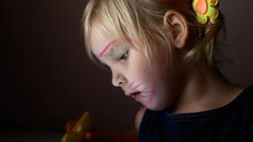 Een klein meisje let op een video De snack en let op de video stock videobeelden