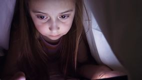 Een klein meisje let op een video die met een deken wordt behandeld stock video