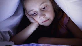 Een klein meisje let op een video die met een deken wordt behandeld stock videobeelden