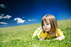 Een klein meisje ligt op een groen gazon op een warme de zomerdag Stock Foto's