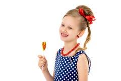Een klein meisje likt lolly stock afbeeldingen