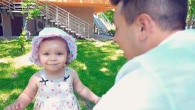 Een klein meisje loopt langzaam langs het groene gazon dichtbij het huis aan haar vader het glimlachen, papa en dochter stock video