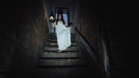 Een klein meisje loopt onderaan de treden in een donkere enge kelder stock video