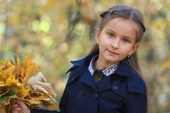 Een klein meisje met een boeket van gele bladeren in handen royalty-vrije stock foto's