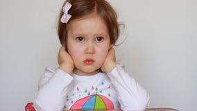 Een klein meisje met een droevig uitdrukkingsgezicht Het kind neemt inbreuk stock footage