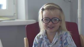 Een klein meisje met glazen speelt met haar broer bij ontbijt stock footage