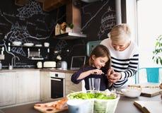 Een klein meisje met grootmoeder thuis het koken stock afbeeldingen
