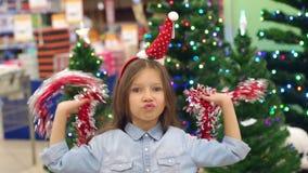 Een klein meisje met een Kerstmanhoed bij haar het hoofd spelen met slingers in supermarkt stock videobeelden