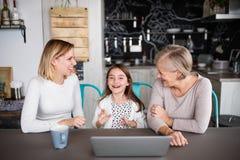 Een klein meisje met moeder en grootmoeder thuis royalty-vrije stock fotografie