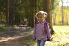 Een klein meisje met een rugzak bevindt zich in een bospark en glimlacht royalty-vrije stock foto