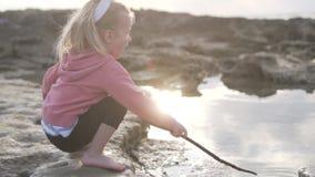 Een klein meisje, met een stok in haar handen stock footage