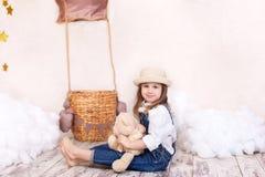 Een klein meisje in overall zit op de vloer met een teddybeer op de achtergrond van een ballon en wolken Het meisje is dreami royalty-vrije stock fotografie