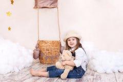 Een klein meisje in overall zit op de vloer met een teddybeer op de achtergrond van een ballon en wolken Het meisje is dreami royalty-vrije stock foto