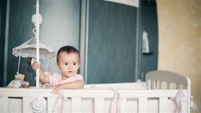 Een klein meisje ploetert in de voederbak en glimlacht zoet HD stock video