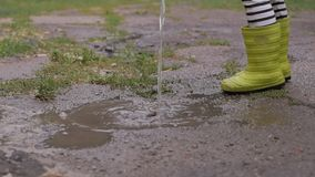 Een klein meisje in regenachtig weer giet in een vulklei van water van een gieter stock video
