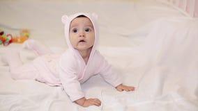Een klein meisje in een roze draagt kostuum liggend op een witte deken stock footage