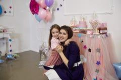 Een klein meisje in een roze jasje en een poederrok is omhelzingen haar mo royalty-vrije stock afbeeldingen