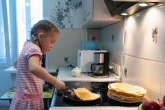 Een klein meisje in een roze kleding braadt pannekoeken op een elektrisch fornuis stock afbeeldingen