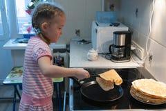 Een klein meisje in een roze kleding braadt pannekoeken op een elektrisch fornuis royalty-vrije stock foto