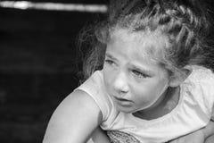 Een klein meisje schreeuwt, rolt een scheur haar wang naar beneden stock afbeelding