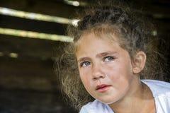 Een klein meisje schreeuwt, rolt een scheur haar wang naar beneden stock fotografie