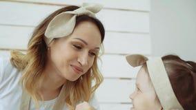 Een klein meisje smeert haar mamma` s neus met bloem stock video
