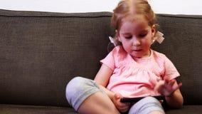 Een klein meisje speelt met een smartphone en wil niet met een lepel eten stock videobeelden