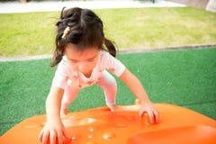 Een klein meisje speelt in speelplaats Stock Afbeeldingen